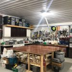 Garage workshop with tools and tubs on the back wall.
