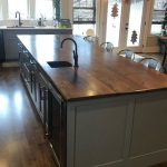 Kitchen with a wooden top island.